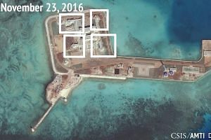 A satellite image shows what CSIS Asia Maritime Transparency Initiative says appears to be anti-aircraft guns on the artificial island Hughes Reef in the South China Sea.