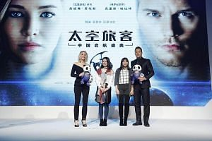 Jennifer Lawrence and Chris Pratt taking pictures with two fans who presented them with panda soft toys at the premiere of Passengers on Dec 17, 2016, in Beijing, China.