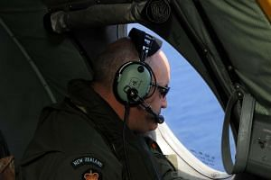 A Royal New Zealand Airforce (RNZAF) P-3K2-Orion aircraft crew member helping to look for objects during the search for missing Malaysia Airlines flight MH370 off Perth, on April 13, 2014.
