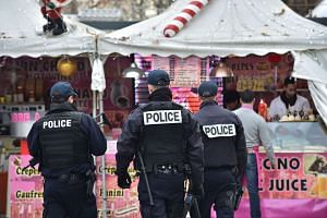 French police officers secure a Christmas market on the Champs Elysees avenue in Paris on Dec 20, 2016.