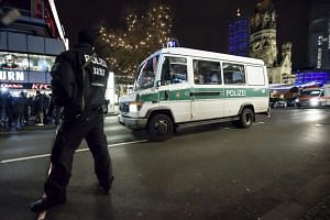 Policemen stand guard at the scene where a truck crashed into a Christmas market in Berlin.