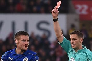 English referee Craig Pawson (right) shows a red card to Leicester City's English striker Jamie Vardy for his challenge on Stoke City's Senegalese striker Mame Biram Diouf during the English Premier League football match in Stoke-on-Trent, central En