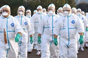 Quarantine officials in protective gear heading to a poultry farm in Kawaminami, Miyazaki prefecture, to bury culled chickens on Dec 20, 2016.