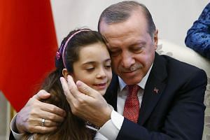 A handout picture taken and released by the Turkish Presidential press office on Dec 21, 2016 shows Turkey's President Recep Tayyip Erdogan (right) posing as he holds in his arms the seven-year-old Bana al-Abed (left), who tweeted from Aleppo on the