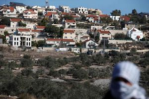A Palestinian protester is seen in front of the Israeli settlement of Qadumim (Kedumim) on Dec 9, 2016.