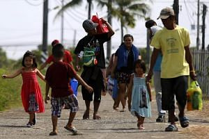 Filipino villagers with their belongings walk at a coastal village on Christmas Day in Cavite city, Cavite province, Philippines, on Dec 25, 2016.