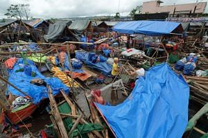 Life goes on in the Philippines a day after the typhoon on Dec 26, 2016, as market vendors retrieve their wares at a damaged market in the town of Polangui.