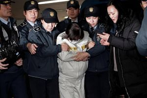 Choi Soon Sil (centre) arrives for questioning into her suspected role in political scandal at the office of the independent counsel in Seoul, South Korea, on Dec 24, 2016.