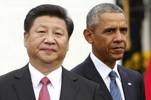 US President Barack Obama (right) stands with Chinese President Xi Jinping during an arrival ceremony at the White House in Washington, on Sept 25, 2015.