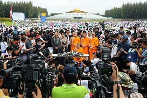 The Department of Special Investigation (DSI) officers (centre, left) and Dhammakaya's Buddhist monks (centre, right) speaking during a press conference at the Dhammakaya Temple in Pathum Thani province, Thailand, on June 16, 2016.