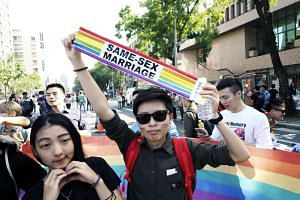 LGBT community members display a rainbow banner outside the Taiwan Parliament building in Taipei on Dec 26, 2016.