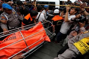 Police officers move the body of one of the robbery victims into an ambulance in Jakarta, Indonesia, on Dec 27, 2016.