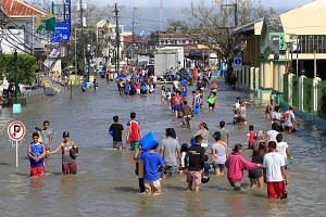 Residents making their way along a street flooded by heavy rain brought by Typhoon Nock-Ten, which cut through Naboa town in the Bicol region of central Philippines yesterday. More than 400,000 people had to be evacuated from their homes due to the t