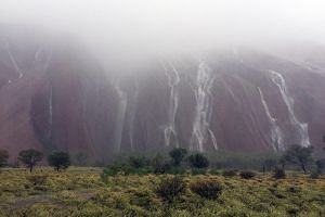 Waterfalls caused by heavy rain running down the side of Australia's famous Uluru rock formation on Monday.