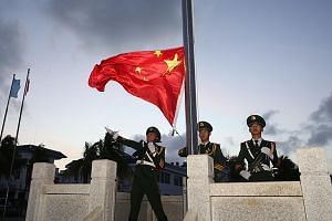 Soldiers conducting a flag-raising ceremony at Chinese-occupied Woody Island in the Paracels yesterday morning. Similar ceremonies were conducted at other disputed islands in the Paracels and the Mischief Reef in the Spratlys. China's assertive claim