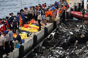 Police officers and rescue workers preparing to remove body bags at Muara Angke port in Jakarta yesterday. A boat carrying hundreds of local tourists caught fire shortly after it left port to head to the popular holiday island of Tidung, the national