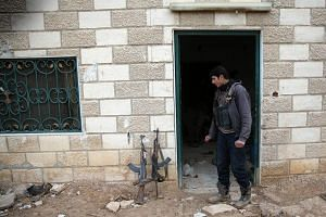 A rebel fighter standing near weapons on the forth day of the truce, on al-Rayhan village front near the rebel held besieged city of Douma, in the eastern Damascus suburb of Ghouta, Syria, on Jan 2, 2017.