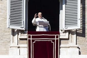 Pope Francis waves from a window at the Vatican on New Year's Day 2017.