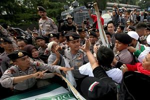 Police officers trying to calm down protesters who gathered to demonstrate against Jakarta governor Ahok (above) outside the trial venue yesterday.