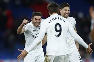 Swansea City's Fernando Llorente, Angel Rangel and Federico Fernandez celebrate after the game.