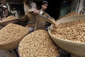 A Pakistani vendor sells peanuts by the road in Peshawar on Jan 2, 2017.