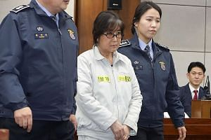 Choi (in beige) appearing on the first day of her trial at the Seoul Central District Court yesterday. She is accused of colluding with Ms Park, whose powers have been suspended, to pressure big businesses into contributing to non-profit foundations