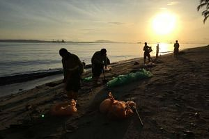 Cleaners at Changi Beach on Friday morning (Jan 6). More than 200 personnel have been involved in a major cleanup of Singapore's north-eastern coast, where the authorities found beaches covered with a black, tar-like substance after an oil spill in J
