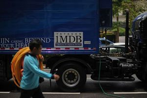 A worker walking past a poster of the 1MDB logo on a truck in Kuala Lumpur, on March 14, 2016.