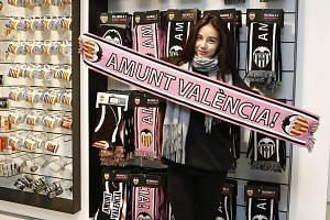 """Kim, the 24-year-old daughter of Valencia owner Peter Lim, holding a scarf with a phrase that translates to """"Go Valencia""""."""