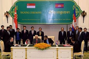 ITEES CEO Tan Seng Hua (left) and Cambodian Labour and Vocational Training Minister Ith Sam Heng (right) during a signing ceremony at the Peace Palace in Phnom Penh on Jan 9, 2017, while President Tony Tan and Cambodian Prime Minister Hun Sen look on
