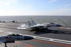 A Chinese J-15 fighter jet landing on the deck of the Liaoning aircraft carrier during military drills in the Bohai Sea, off China's northeast coast.