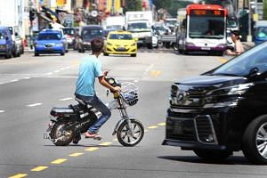 An e-biker riding against the flow of traffic in Geylang.
