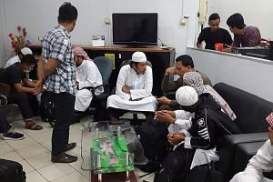 Left: Five of the eight deported men (wearing headgear and white robes) being questioned by the Indonesian authorities in the Riau Islands on Tuesday. The men were deported to Malaysia and sent to Indonesia after officers at Woodlands Checkpoint foun