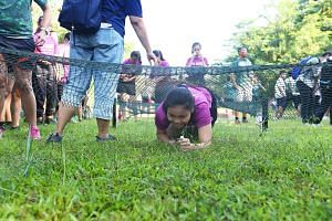 At the launch of the ActiveSG Outdoor Adventure Club yesterday, participants could try out an obstacle course (above) as well as learn various skills such knot tying (left).