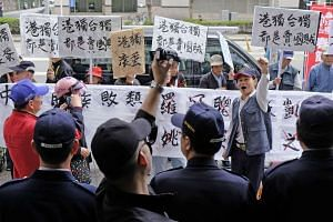 Pro-unification activists display placards and banners in front of the police outside a political forum venue hosted by Taiwan's grassroot New Power Party in Taipei on Jan 8, 2017.