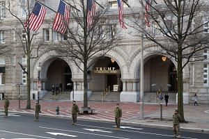 Members of the US military stand in front of the Trump International Hotel Pennsylvania Ave. during an inaugural parade rehearsal on Jan 15, 2017 in Washington, DC.