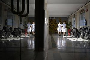Two staff nurses walk down a corridor outside an almost empty ward at Alexandra Hospital on June 29, 2015.