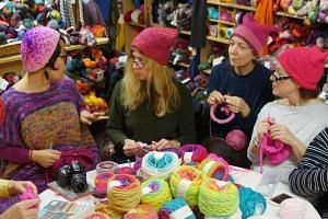 A group of women gather at Knitty City in New York to make their pink Pussyhats in preparation for protests for women's rights following the election of Donald Trump.