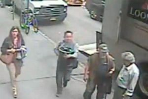 A still frame from NYPC surveillance video shows a man carrying a 86-pound pail of gold flakes valued at $1.6 million off an armored truck in Manhattan, New York, US.