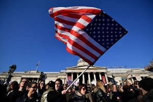 A protester waves the US flag during the Women's March in Trafalgar Square in London on Jan 21, 2017.