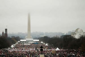 The top of the Washington Monument is shrouded in clouds as people pack the National Mall for the Women's March in Washington, DC, on Jan 21, 2017.