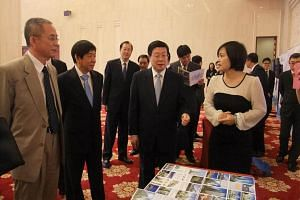 Tianjin Mayor Huang Xingguo (centre) and then-Minister for National Development Khaw Boon Wan (second from left) visiting an exhibition in Tianjin, China on July 30, 2014.