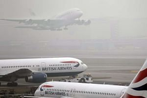 Planes of the British Airways airline on the runway as thick fog delays departures from Terminal 5 Heathrow Airport in London, Britain, on Jan 23, 2017.