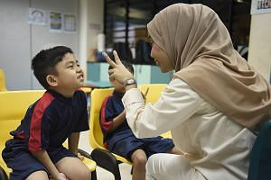 Eight-year-old Aqil Nabil Maulid gave his teacher Hanysah Ismail, 45, a big smile yesterday on his sixth day of school. The boy, who has autism, was homeschooled last year while waiting for a place in Eden School, which caters specifically to childre