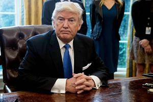 US President Donald Trump looks on after signing executive orders in the Oval Office at the White House in Washington, DC, on Jan 24, 2017.