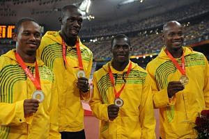 A 2008 photo shows Jamaica's Usain Bolt posing with his relay gold with team-mates Michael Frater, Asafa Powell and Nesta Carter.