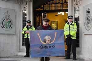 Political satire artist Kaya Mar with a painting depicting British PM Theresa May outside the Supreme Court in London, on Tuesday. What the court has done in this case is no different to what it does every day: It decided on what it considers to be t