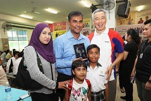 PM Lee with Mr Aziz bin Ahmad and his family earlier this month. Mr Aziz's son Adam had just received a bursary from PM Lee, who, 31 years ago, had presented the father himself with a similar bursary.