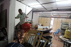 Mr Lam Jie, 67, standing on a chair to avoid the flood waters in his house in Sungai Lembing, Kuantan, yesterday. His plans for Chinese New Year have been disrupted after flood waters rose to waist-level, ruining many items in his residence. A priest
