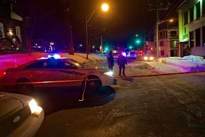 Quebec Provincial and municipal police officers are seen behind a cordoned off area after two gunmen reportedly opened fire at the Quebec Islamic Cultural Centre in Quebec City, Canada, on Jan 30, 2017.